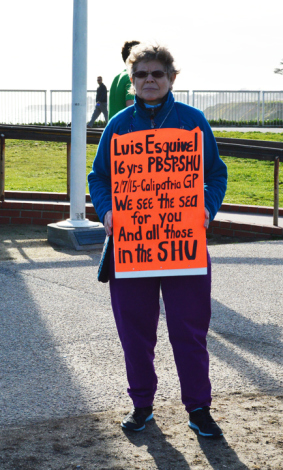 Renowned activist Willow Katz wears a sign citing Luis Esquivel's eloquent plea to simply see the sea.